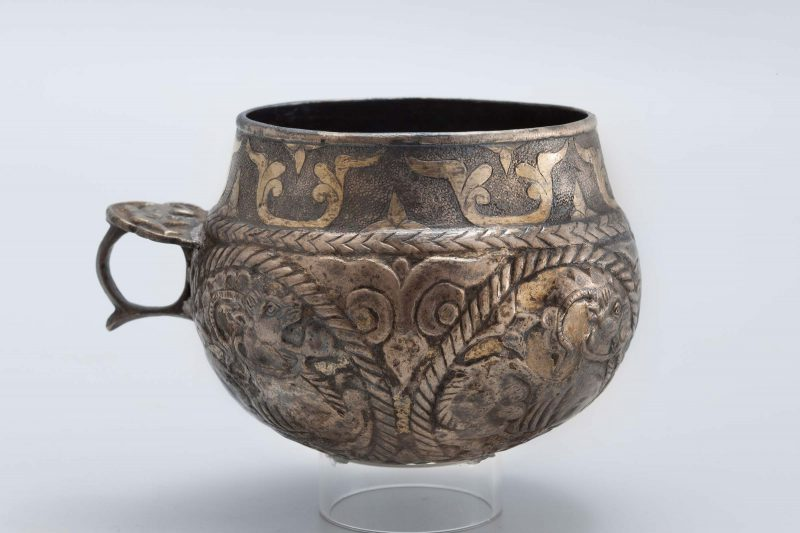 Spherical cup with ring handle. The body of the cup has roundels with goals and a vegetal motif at the rim.