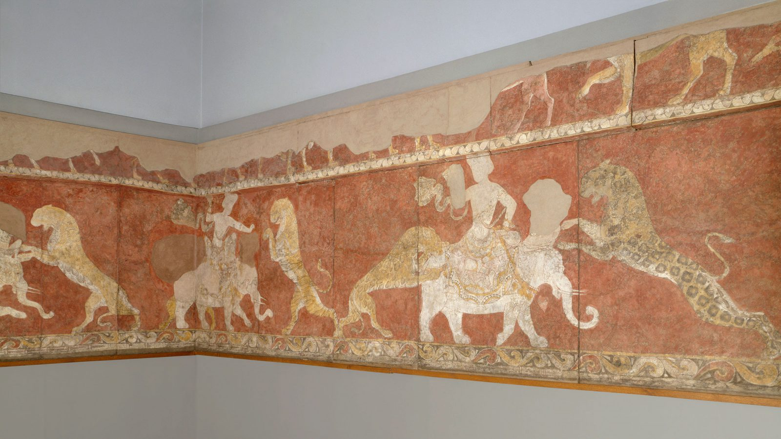 This painting shows a battle between a deity and a beast of prey, possibly leopards. The deity is in the middle, sitting on an elephant as beasts attach from either side.