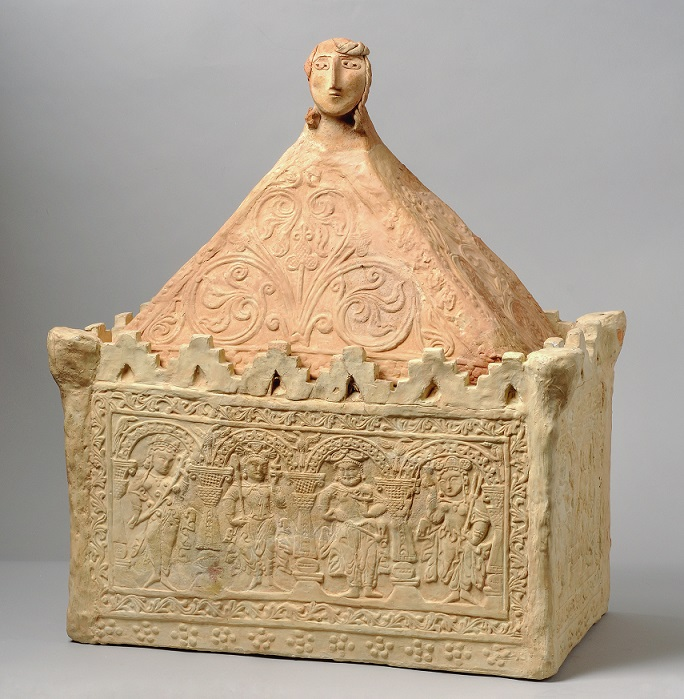 Lidded container with rectangular base with crenelation and figures in an arcade. Triangular lid with depiction of a head at the top.