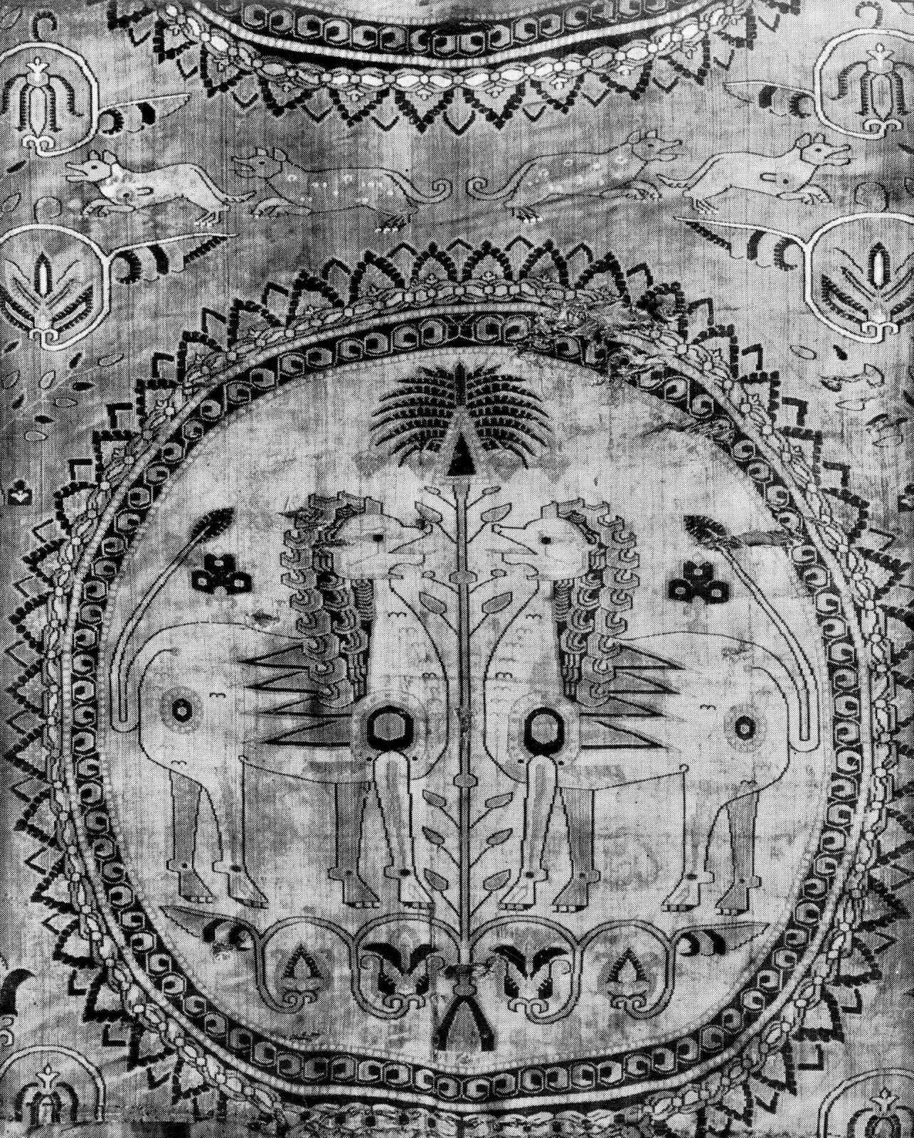 Roundel on a textile with two facing lions separated by a vegetal form