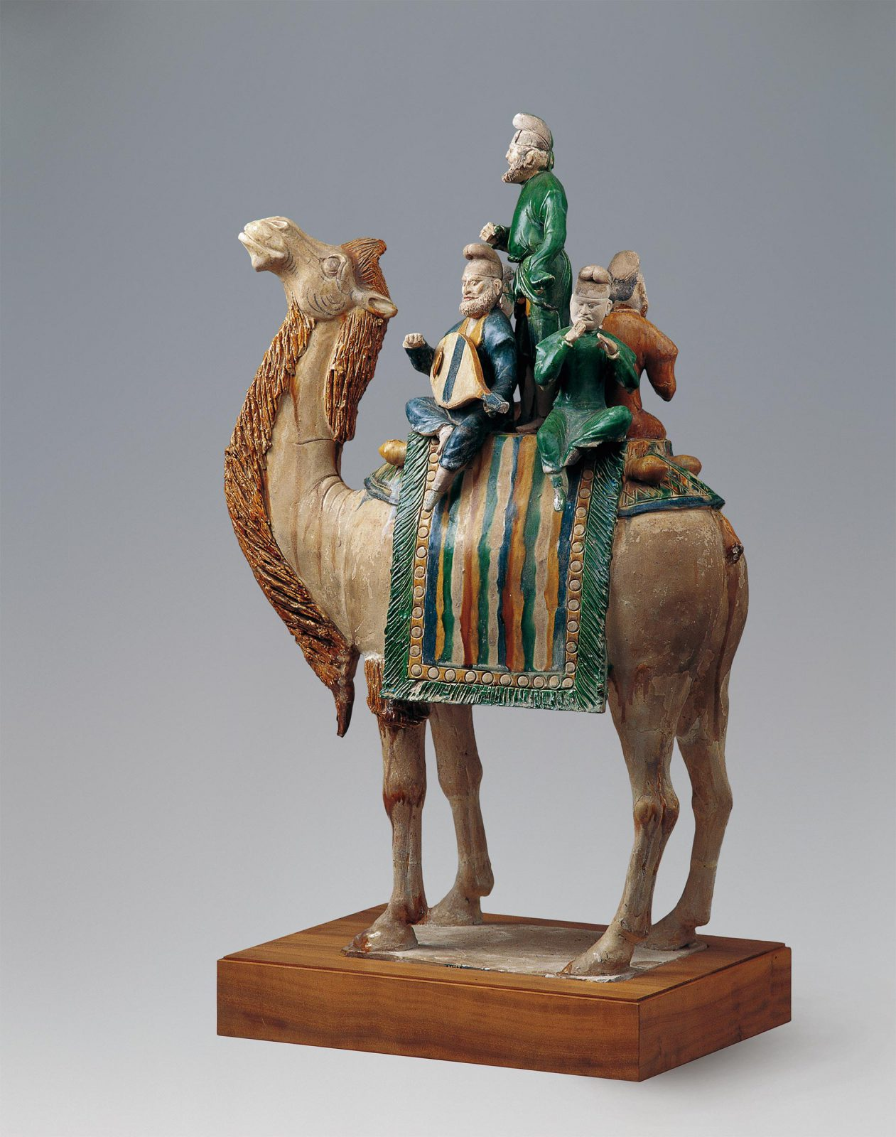 Four musicians on a camel