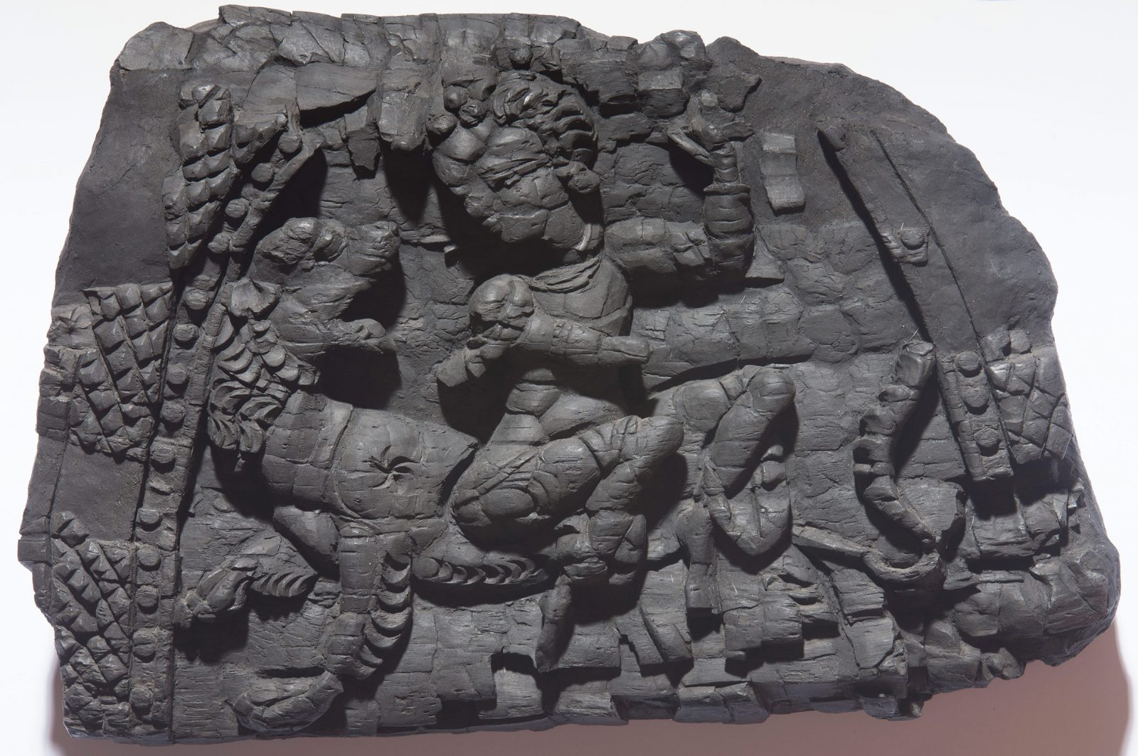 Wooden panel in the shape of a half circle showing a female deity on a lion