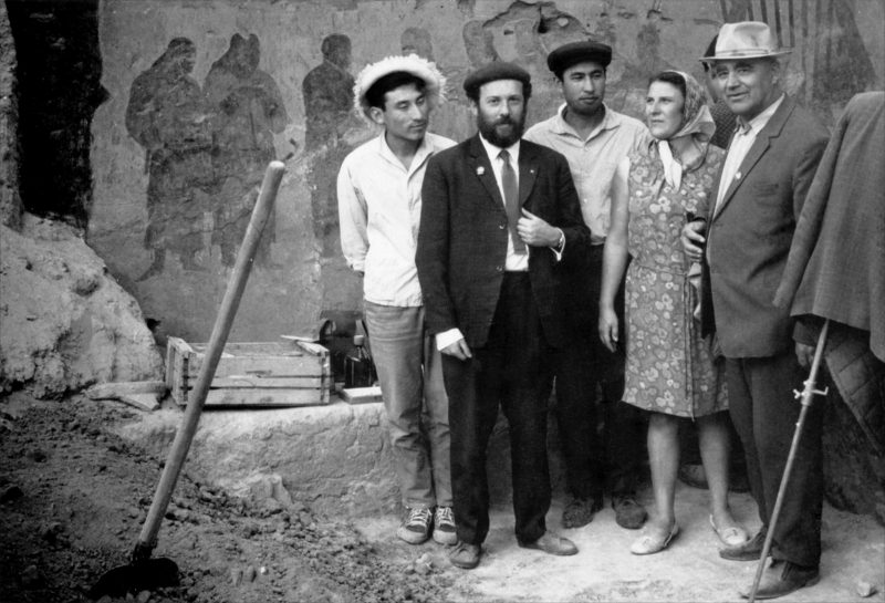 Historic photograph of archaeologists in front of wall paintings