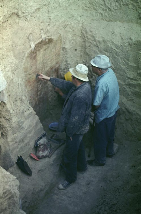 Two archaeologists pointing at wall painting at excavation site
