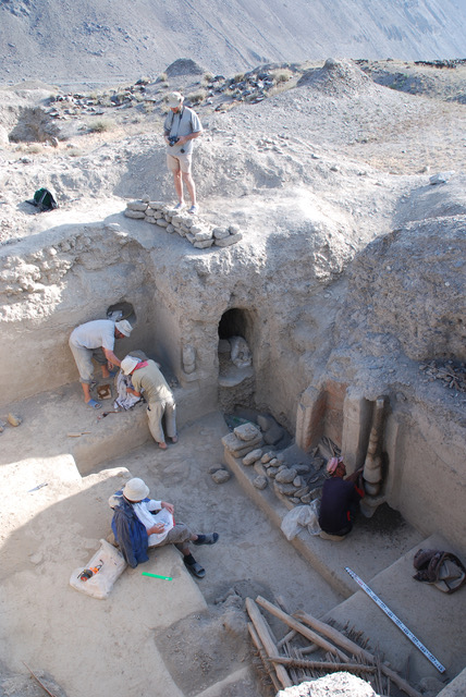 Modern archaeologists surveying a dwelling