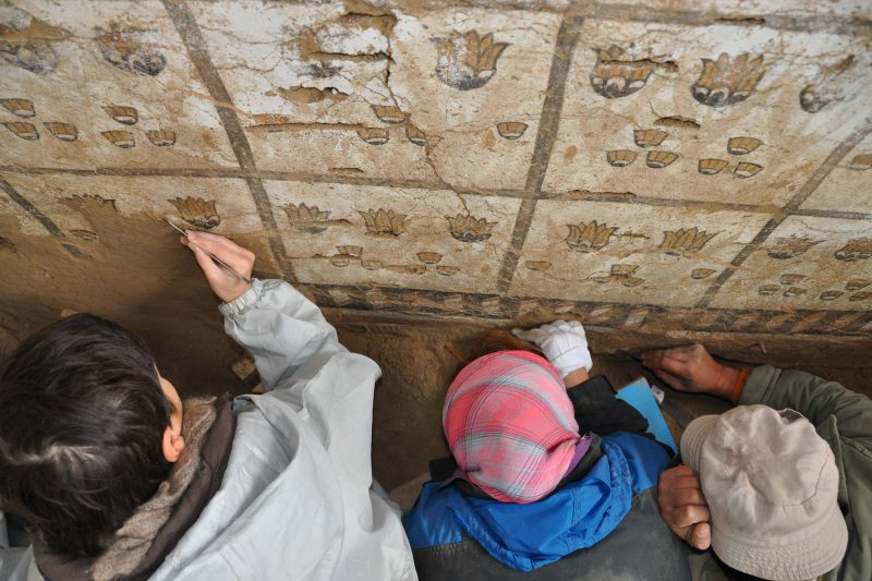 modern archaeologists clean a wall painting