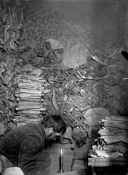 In this photograph, archaeologist Paul Pelliot crouches to examine a manuscripts in the Library Cave (Cave 17) at Dunhuang. Behind him, there are hundreds of rolled manuscripts.