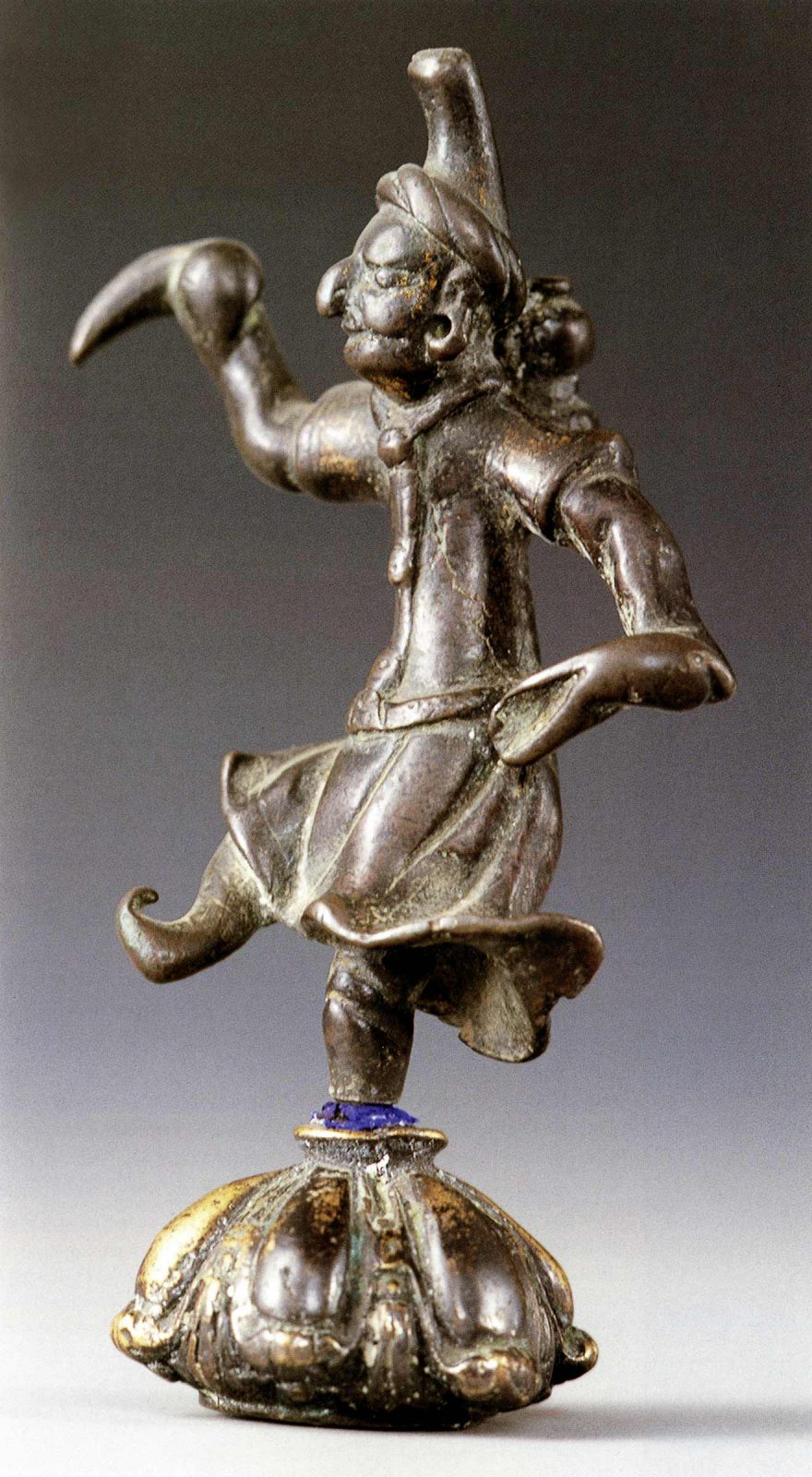 Dancing sculpture of dancer with conical hat and long sleeves
