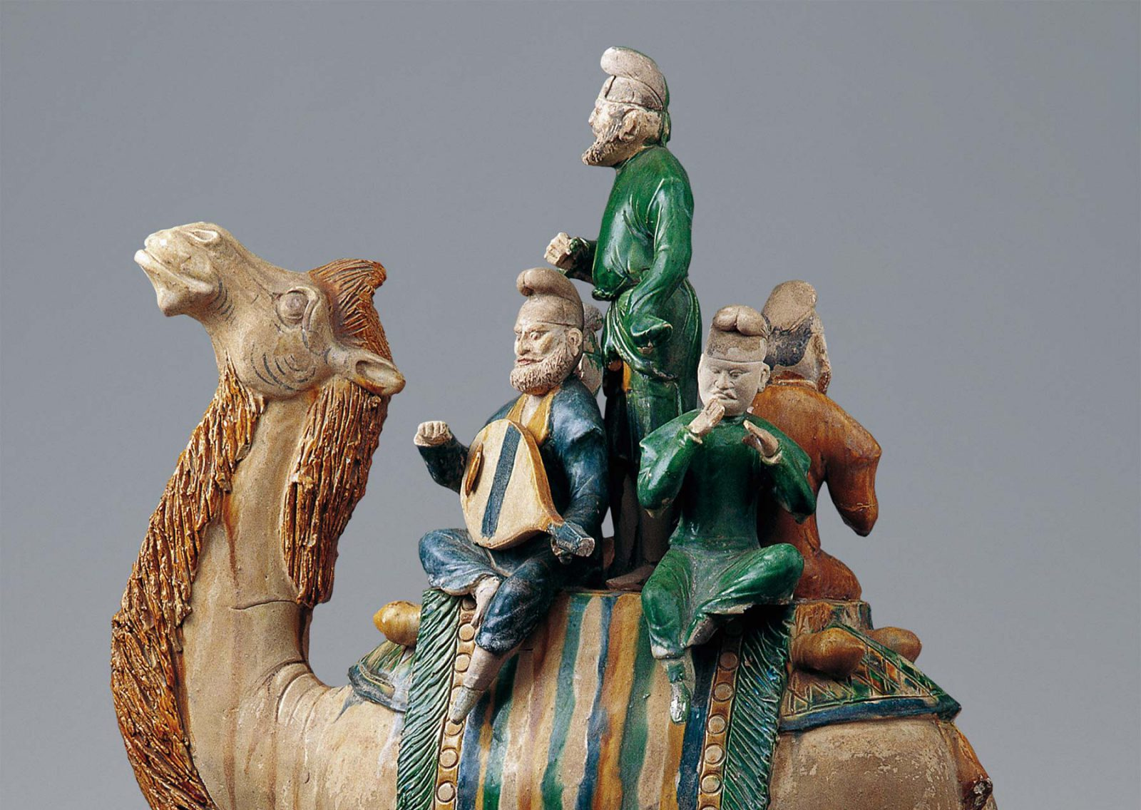 Four musicans on a camel
