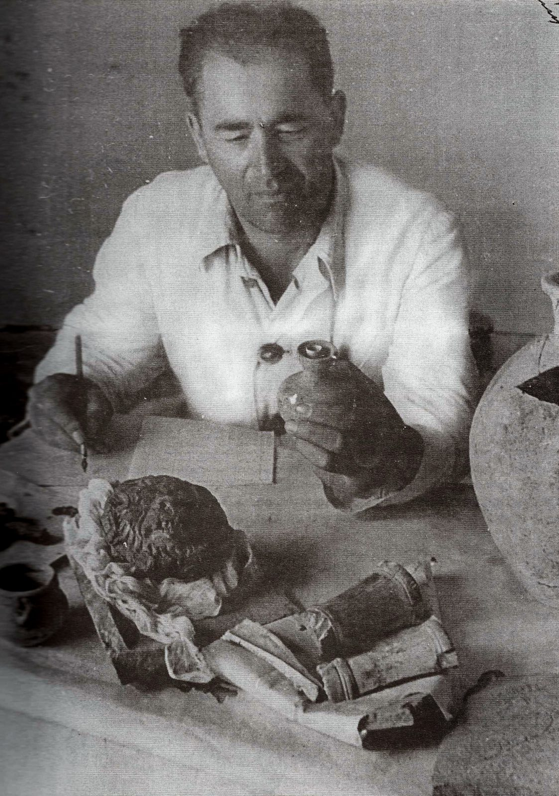 In this photograph, Russian archaeologist Aleksandr M. Belenitsky sits at his work table, examining finds at Panjikent, Tajikistan (in ancient Sogdiana), 1952.