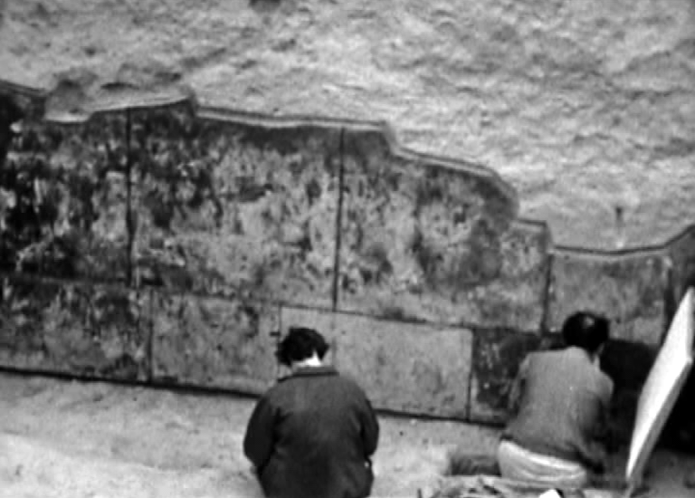 This historic photograph shows the original excavation of the Rustam cycle and two archaeologists working to reveal and document the paintings.