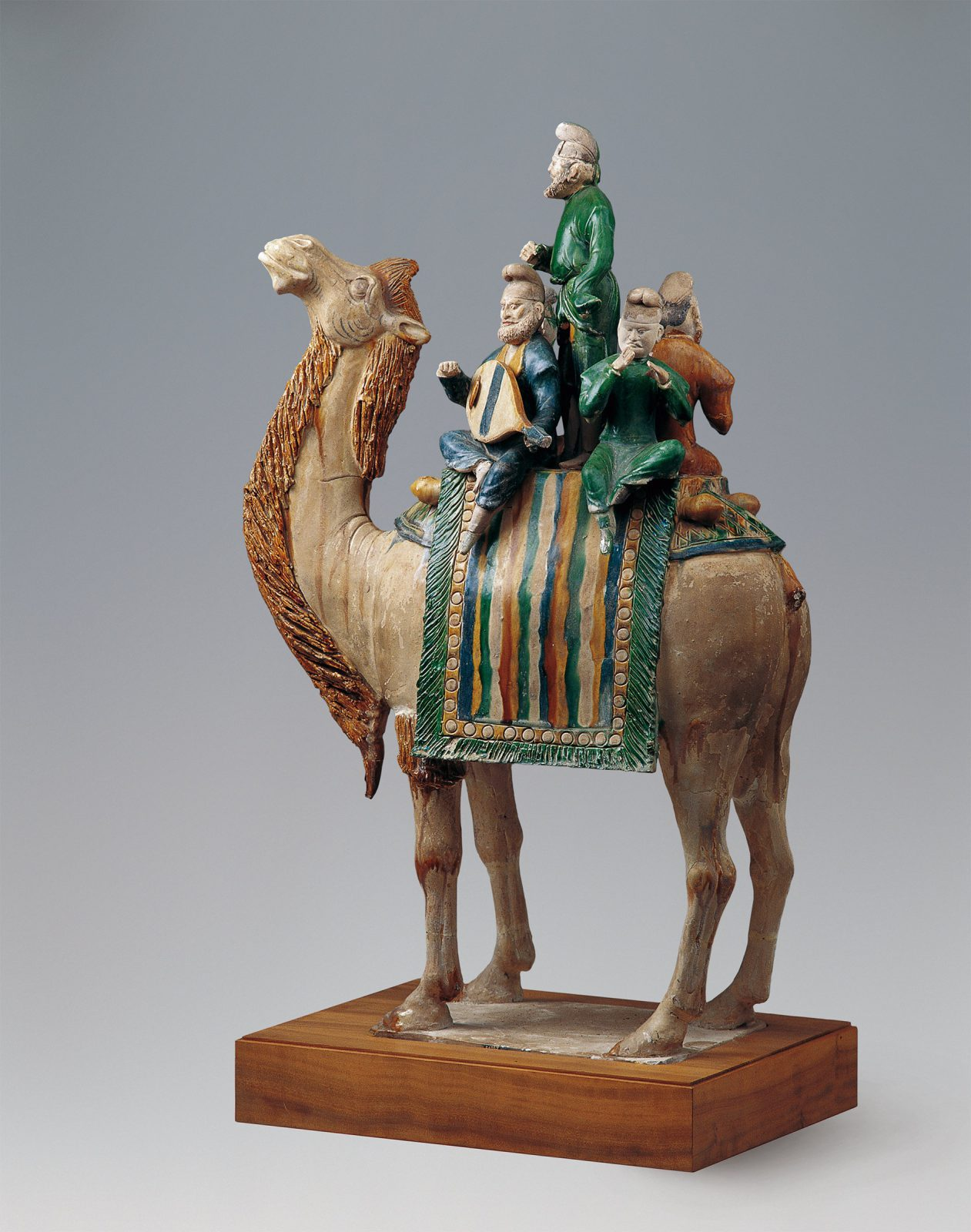 Four musicians sit on a camel and play.