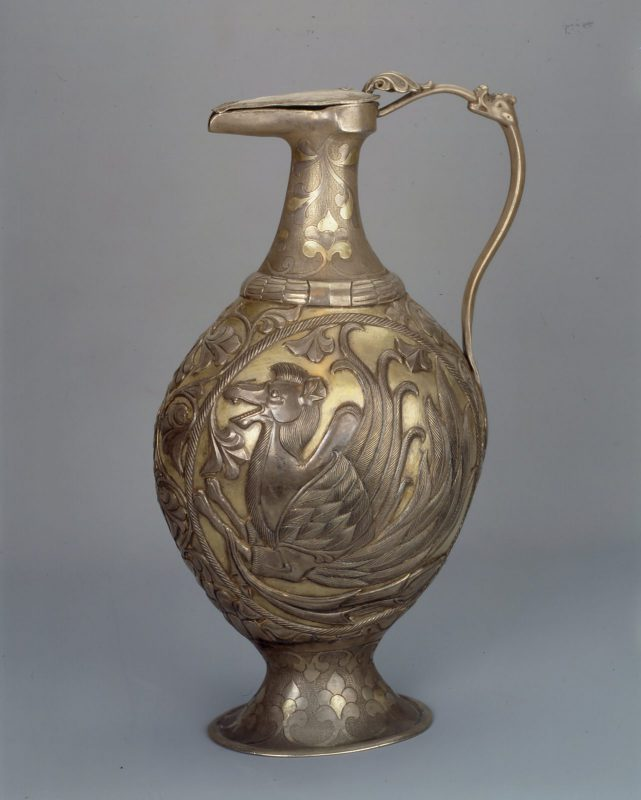 Silver ewer with slender handle. The front the body of the vase features a winged camel.