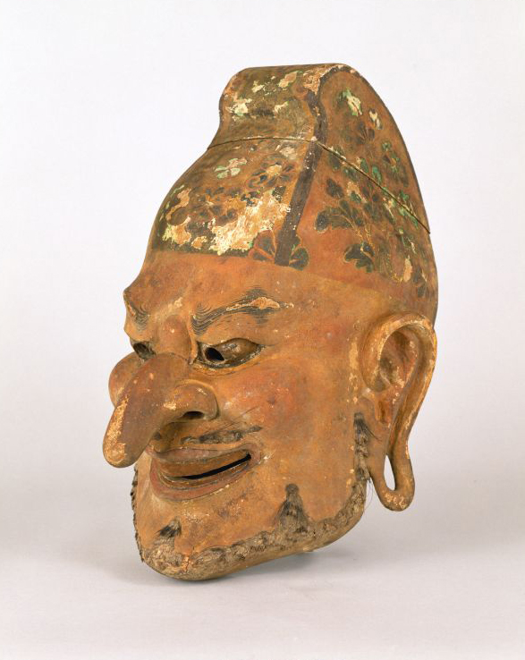 The mask portrays an indvidual with a long nose, extended earlobes, grin, and conical hat